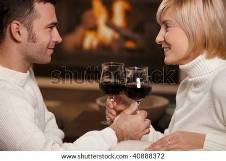 Young romantic couple sitting on sofa in front of fireplace at home, drinking red wine. - stock photo