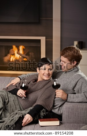 Young romantic couple sitting on sofa in front of fireplace at home, drinking red wine.? - stock photo