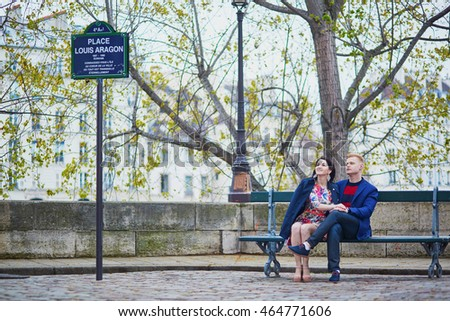 Young romantic couple sitting together on a bench on a Parisian street. Tourists enjoying their vacation in France. Romantic date or traveling couple concept