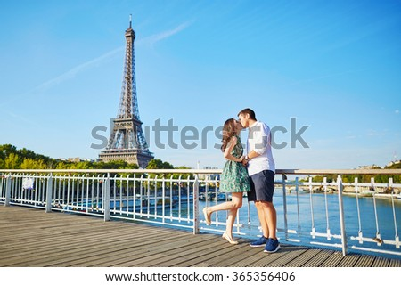Young romantic couple spending their vacation in Paris, France. Dating couple posing near the Eiffel tower - stock photo