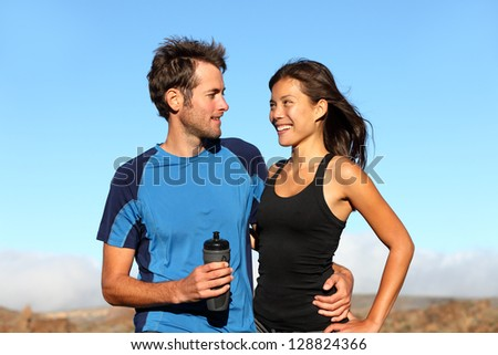 Young romantic healthy athletic couple standing arm in arm taking a break from training in open countryside smiling into each others faces. Multiethnic couple with Asian woman and Caucasian man. - stock photo