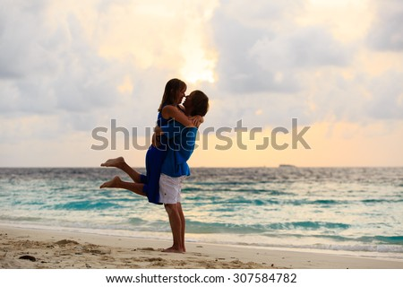 Young romantic loving couple on the beach at sunset - stock photo