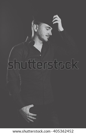 Young romantic man. Men's fashion. Man posing and adjusts his hat. Black and white photography. Profile men. - stock photo