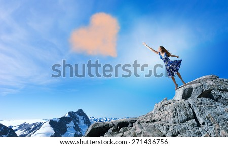 Young romantic woman in summer dress reaching love heart - stock photo