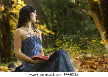 Young Romantic Woman Reading Novel in woodlands - stock photo