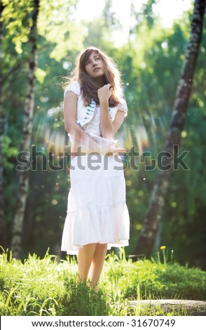 Young romantic woman standing in sun rays.