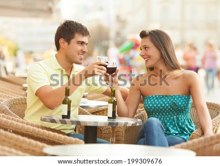 Young romatic couple drinking wine in a cafe - stock photo
