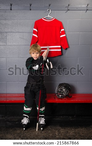 Young Rookie Hockey Player In Dressing Room at Hockey Rink - stock photo