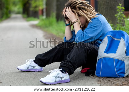 Young rude girl sitting on the road with problems - stock photo