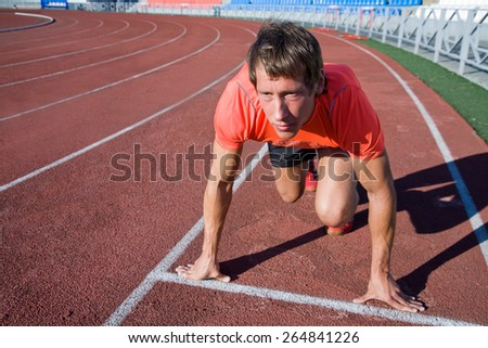young runner at the start on the treadmill at the stadium - stock photo