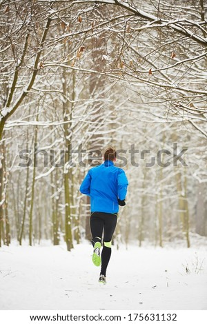 Young runner in winter jogging in park. - stock photo