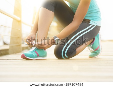 Young runner tying shoe lace on wooden boardwalk at sunrise - stock photo
