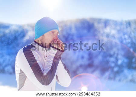 Young runner warms him up while resting during his training outside in sunny winter park - stock photo
