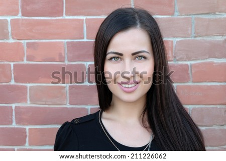 Young 20s brunette head and shoulders front view  against red brick wall, a lot of copyspace - stock photo