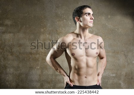 Young 20s man posing showing abdominal muscles with wall backgroundl