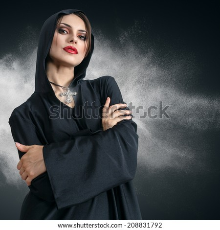 Young sad beautiful woman in black hood with cross