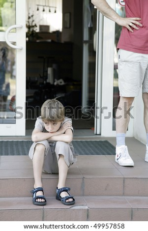 young sad boy sitting on steps - stock photo