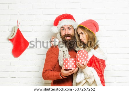 Young sad Christmas or new year couple of bearded man with gift box and pretty sexy girl or beautiful woman in red santa claus costume with xmas bauble and sock on white brick wall