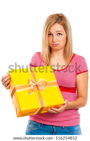 Young sad disappointed woman holding yellow gift box, isolated on white background. - stock photo