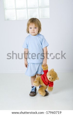 Young sad girl standing and holding teddy bear in hand. She's looking at camera. Front view. - stock photo