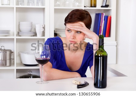 young sad thinkful woman sitting with a glass of red wine in her kitchen - stock photo