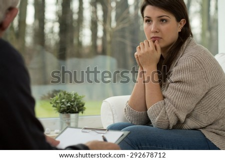 Young sad woman being on psychotherapy session - stock photo