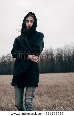 Young sad woman in black cloak walking on the field
