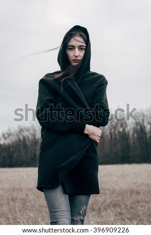 Young sad woman in black cloak walking on the field. Wind - stock photo