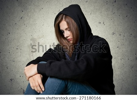 Young. Sad woman in depression and despair crying on black dark background - stock photo