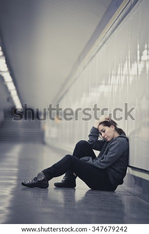 young sad woman in pain sitting alone and depressed at urban subway tunnel ground looking worried and frustrated suffering depression in female loneliness concept  - stock photo