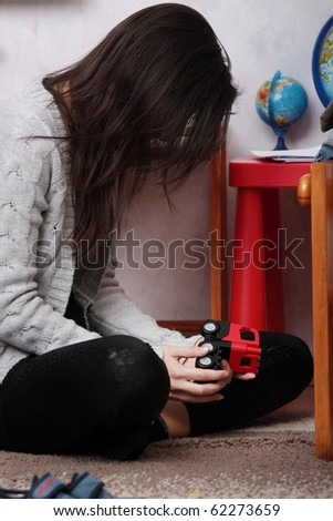 Young sad woman (mother) sitting in children room (lost of child concept) - stock photo