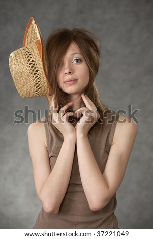 Young sad  woman posing in a studio on a grey background with a cowboy hat - stock photo
