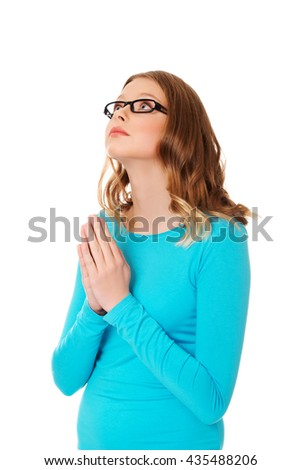 Young sad woman praying holding clasp hands  - stock photo