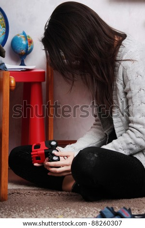 Young sad woman sitting in children room (lost of child concept) - stock photo