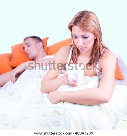Young sad woman sitting on bed and drinking coffee, nearby slept  man. Focus on the woman. - stock photo