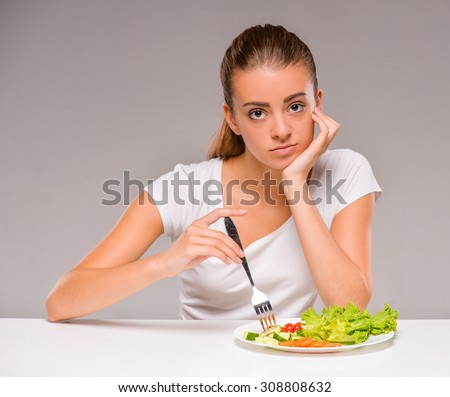Young sad woman with a plate of salad. - stock photo