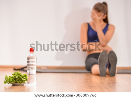 Young sadness woman is sitting on the floor. Focus on salad and bottle of water. - stock photo