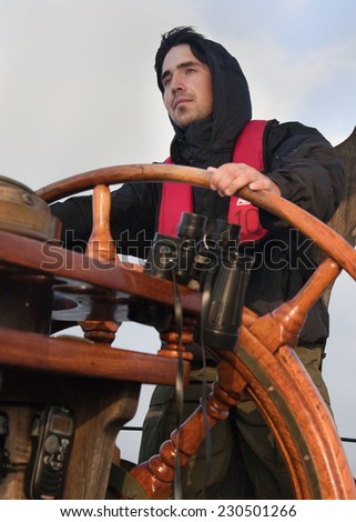 Young sailor on a ship's deck behind a steering wheel - stock photo