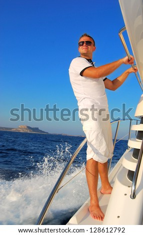 Young Sailor relaxing happily on the vacation sailboat yacht standing on a deck having a rest on summer boat over blue ocean wave splashes background - stock photo
