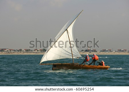 Young sailors in a traditional racing dhow in the Arabian Gulf, off Dubai. - stock photo