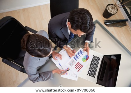 Young sales persons studying statistics in an office - stock photo