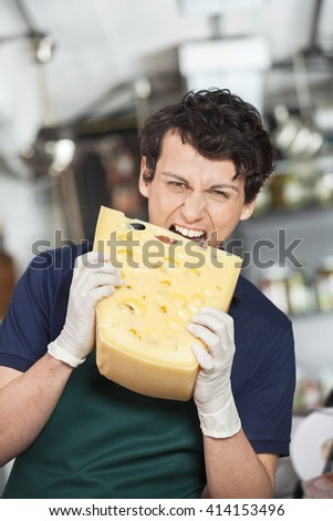 Young Salesman Biting Cheese In Store - stock photo