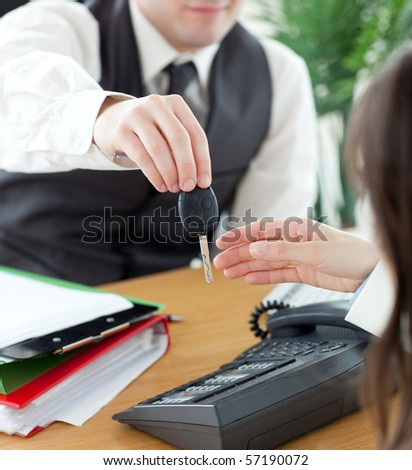 Young salesman giving car's key to his customer in his office - stock photo