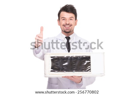 Young salesman is holding quality mattress isolated on the background.