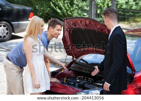 Young salesman showing new car engine to couple at dealership - stock photo