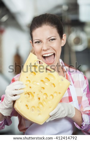Young Saleswoman Biting Cheese In Store - stock photo