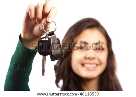 Young saleswoman handing over car keys, isolated on white background