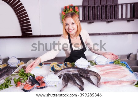 young saleswoman offers fresh fish in a shop - stock photo