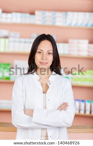 young saleswoman with folded arms working in a drug store