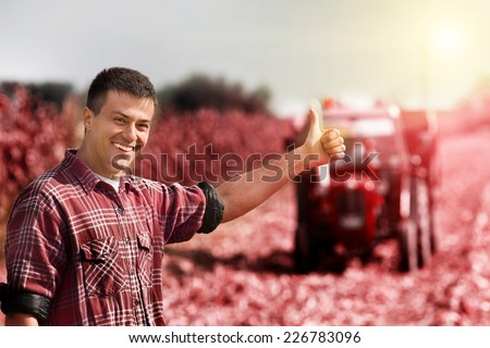 Young satisfied farmer showing thumbs up, tractor in field in background - stock photo